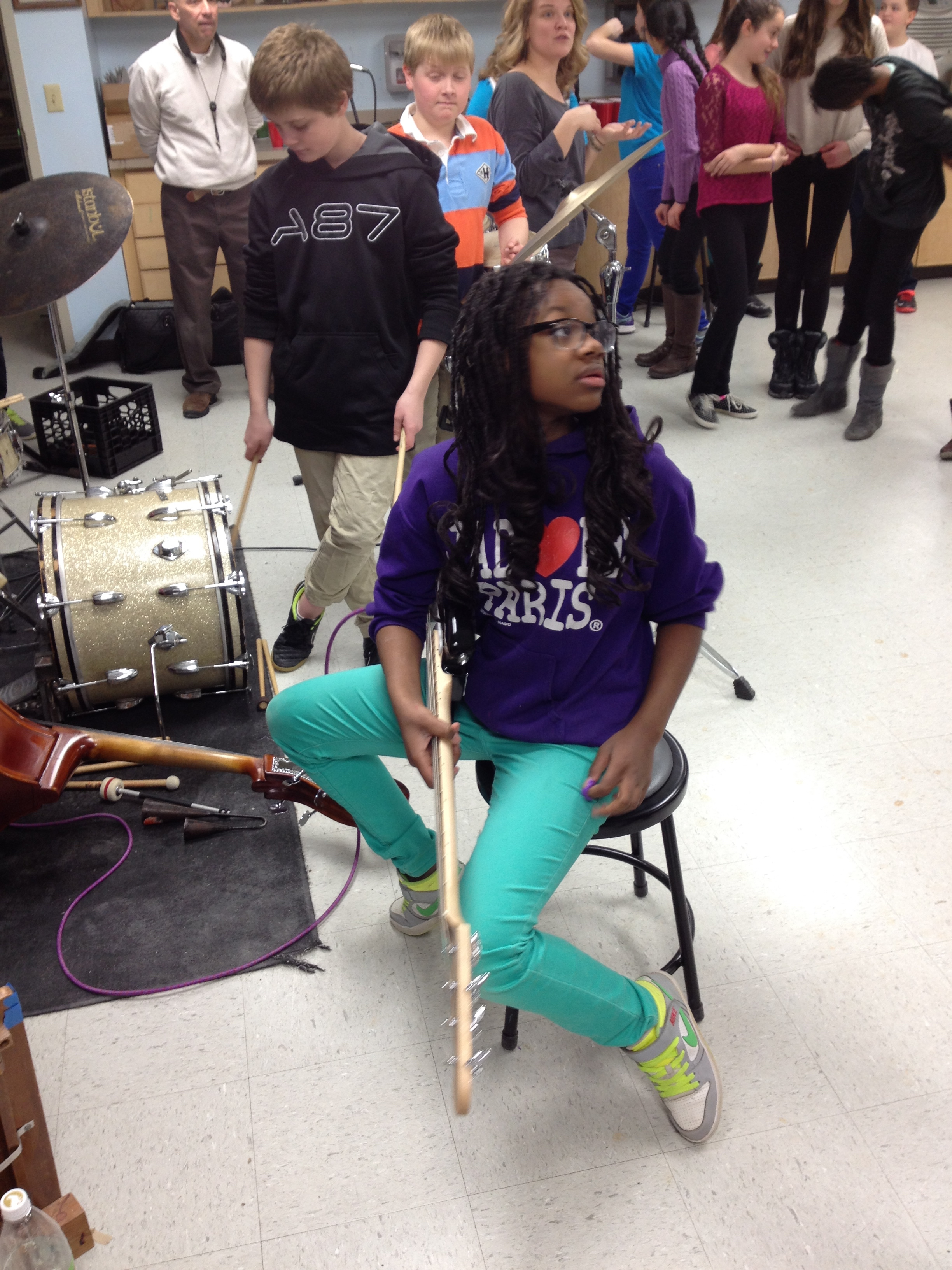 Young bassist listens intently as we compose a song to be performed in music and paint